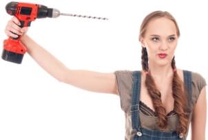 Mladá žena s aku vrtačkou míří vrtákem ke své hlavě
