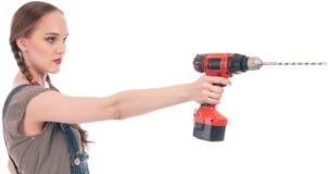 Mladá žena drží aku vrtačku v napřažené pravé ruce