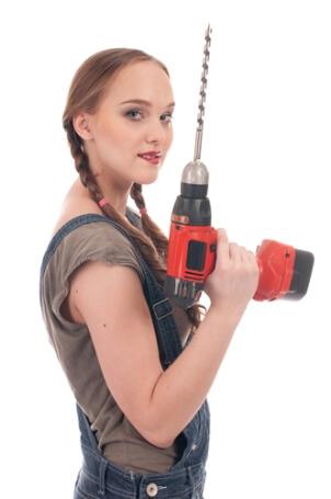 Mladá žena drží aku vrtačku před sebou vrtákem vzhůru